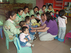 Caregivers and toddlers gathered in a classroom